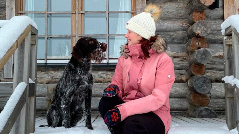 Koira ja nainen talvisen kelomökin lumisella kuistilla