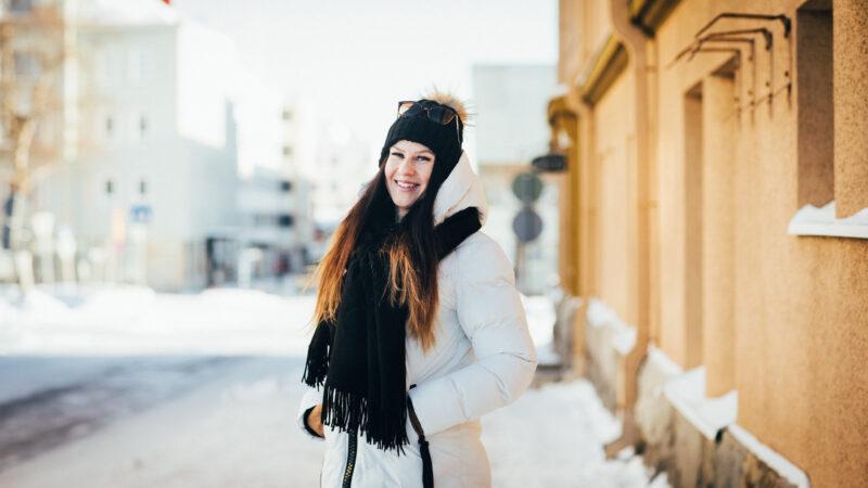 Henkilö hymyilee Kajaanin kaupungin kadulla